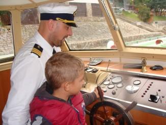 Malí pasažéři si prohlíží kormidelnu